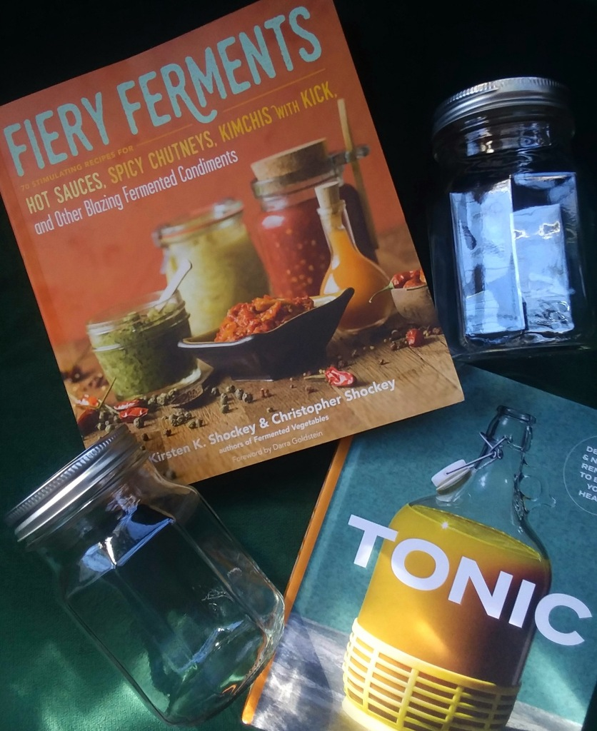 two canning jars and two fermenting cookbooks on a green background