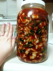 gallon jar of kimchi with a hand nearby to show size
